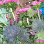a brown eye with glasses visible through flowers